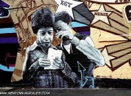 A mum reading a paper with a boy. | Long Island | 5 Pointz | New York Murales